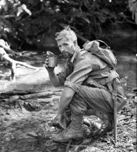 PRIVATE H.E. NEWMAN OF THE 2/33RD AUSTRALIAN INFANTRY BATTALION STOPS BY FOR A DRINK DURING A PATROL BETWEEN NAURO AND MENARI.