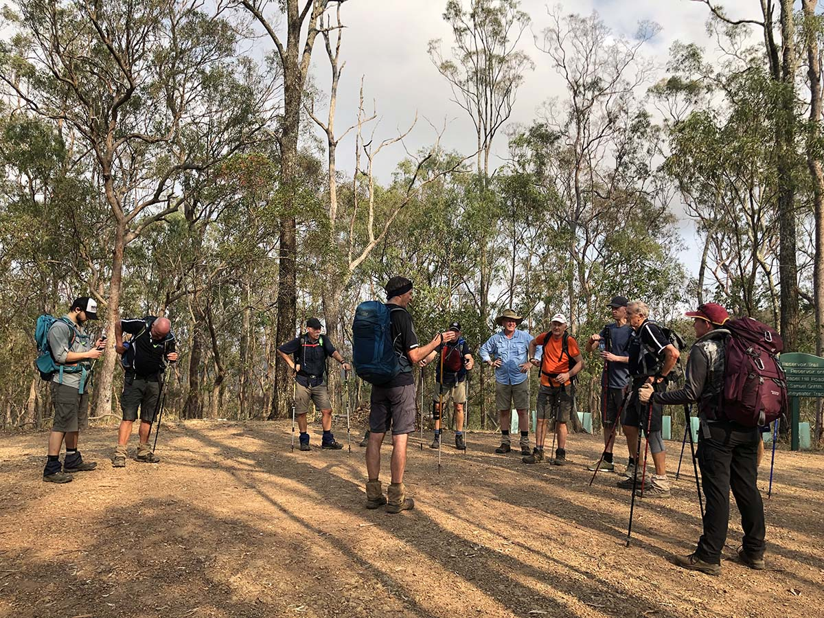a group of trekkers standing in a circle in the Australian bush